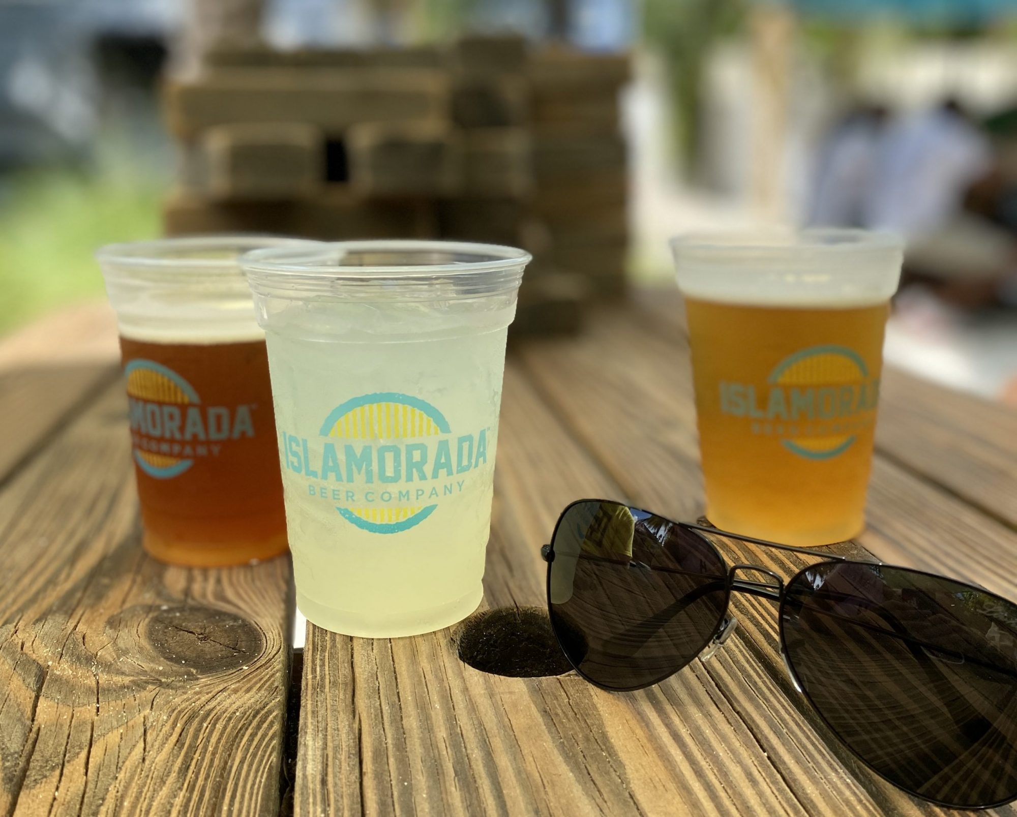 verres de bières fraiches sur une table en bois dans le patio de la Islamorada Brewery and Distillery. Une adresse des Keys recommandée par Miami Off Road