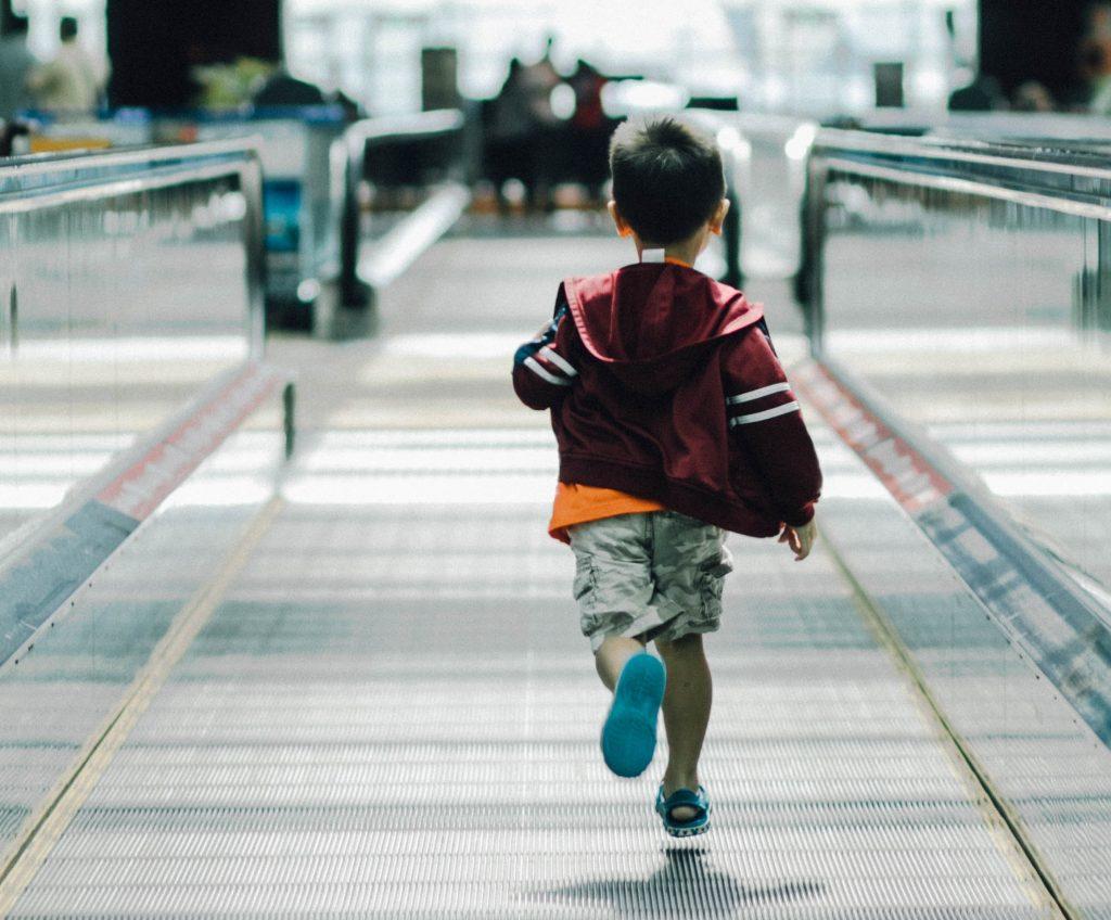enfant courant dans un aéroport. Les conditions de voyage des moins de 12 ans suite a la réouverture des frontières américaines. Miami Off Road vous dit tout.